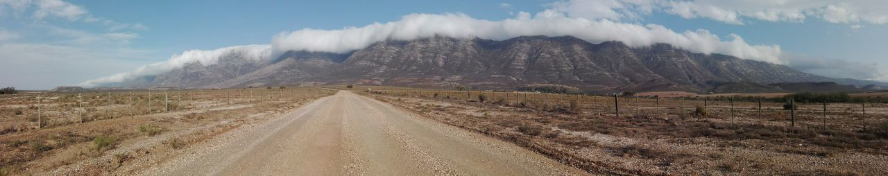 Panoramic view of dirt road along landscape