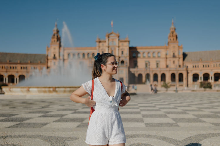 Young tourist woman wearing a white dress is looking away and smiling while standing in seville.
