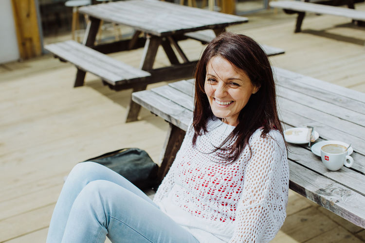 High angle portrait of smiling woman sitting on picnic table
