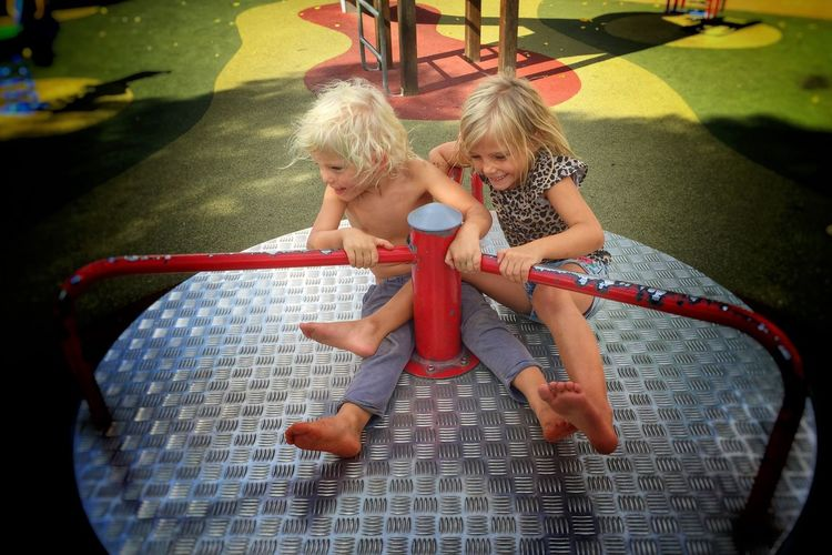 High angle view of happy siblings sitting on merry-go-round at park