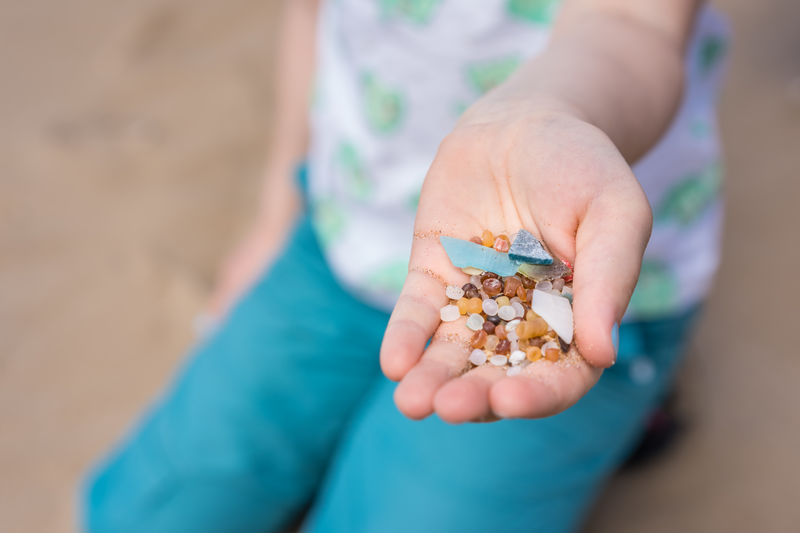 Midsection of child holding crystals while kneeling at beach