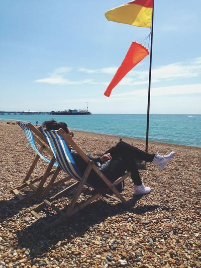 Soaking up the sun Wind Brighton Travel Destinations Lifestyles Realxing Break British Trendy Ocean Pebbles Lounging Sitting No Face Casual Girl Woman Beach Chair Water Sea Beach Sky Land Nature Horizon Tranquil Scene Tranquility Sunlight Outdoors Sand Flag