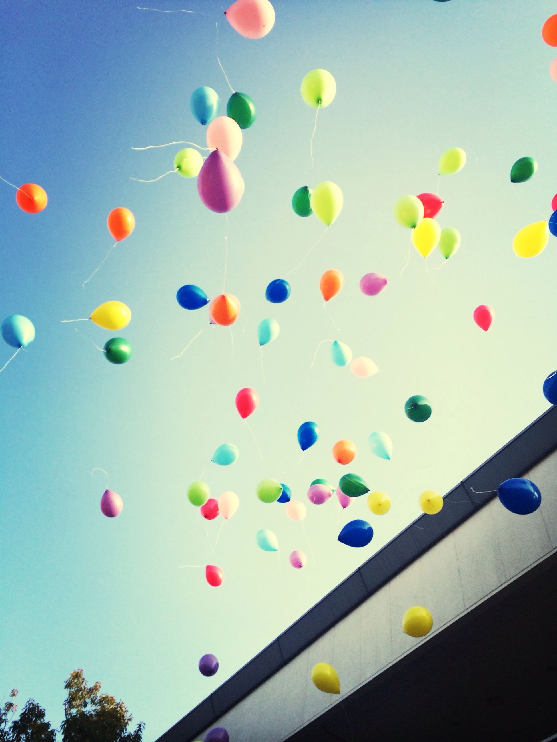 multi colored, colorful, balloon, variation, blue, mid-air, low angle view, celebration, large group of objects, hot air balloon, sky, in a row, no people, abundance, childhood, outdoors, pattern, circle, decoration, high angle view
