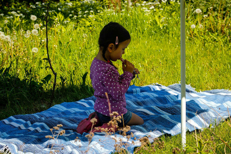 Side view of girl eating while kneeling on picnic blanket amidst grass
