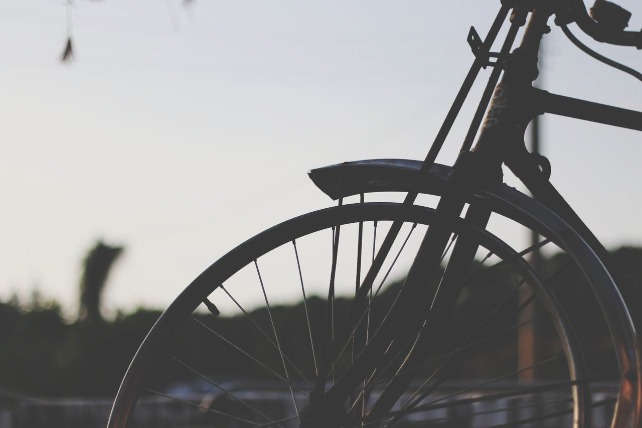bicycle, transportation, wheel, land vehicle, mode of transportation, focus on foreground, spoke, day, sky, no people, tire, stationary, nature, outdoors, close-up, clear sky, metal, travel, selective focus, copy space