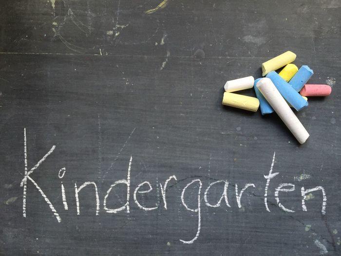 Multi colored chalks on blackboard by kindergarten text