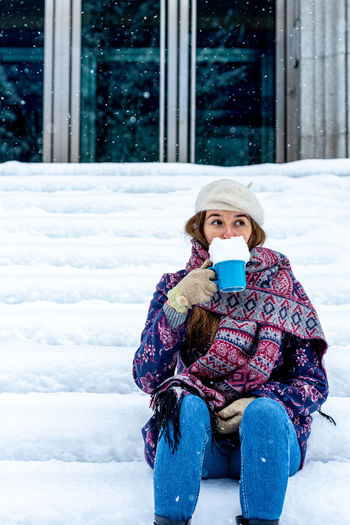 Woman holding coffee cup in snow