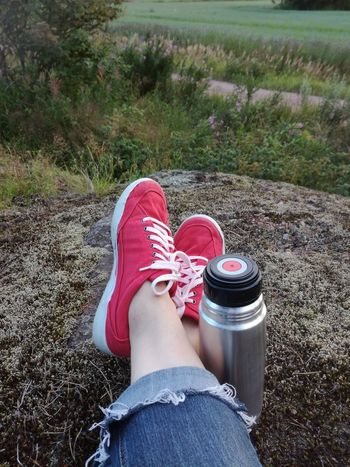 Low Section Human Leg Personal Perspective One Person Human Body Part Jeans Canvas Shoe Day Real People Leisure Activity Red One Woman Only Outdoors Summer Thermos Coffee Break Rock Field Rural Finland Red Shoes Relaxing Moments