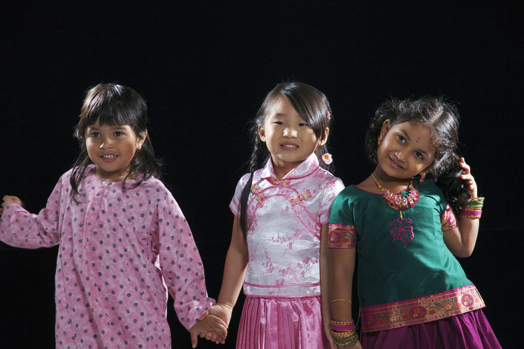 Portrait of smiling girls standing against black background