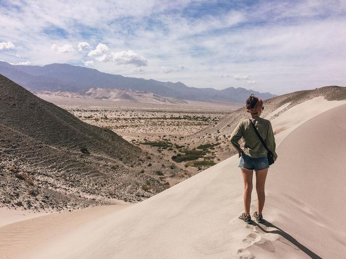 Full length of woman standing on sand dune against sky