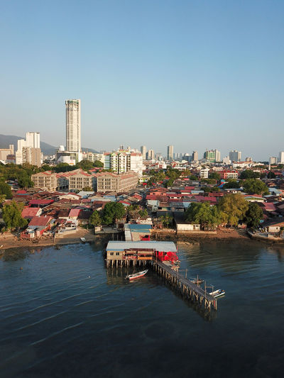 Scenic view of river and buildings against clear sky