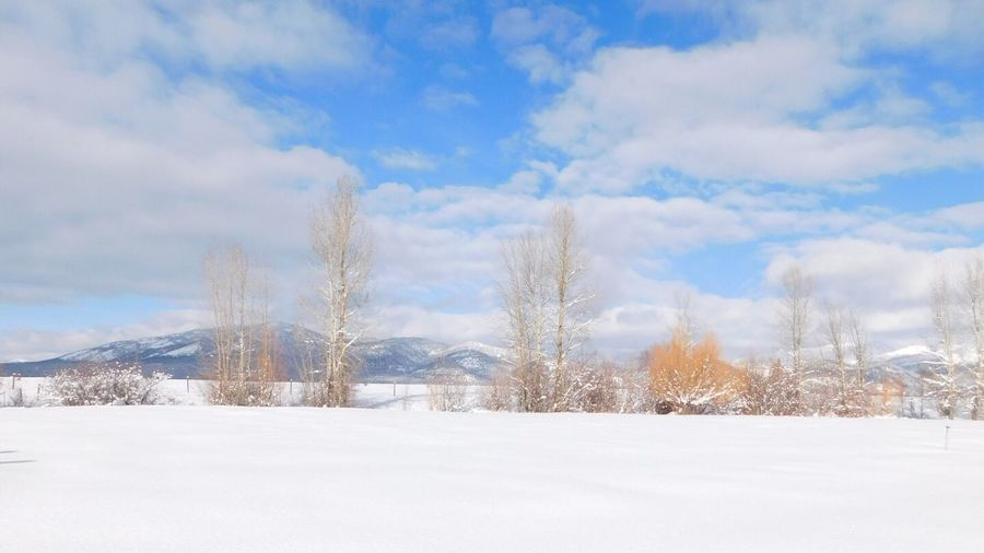 Snow covered landscape against cloudy sky