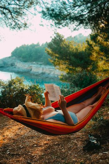 Woman lying down on hammock by trees