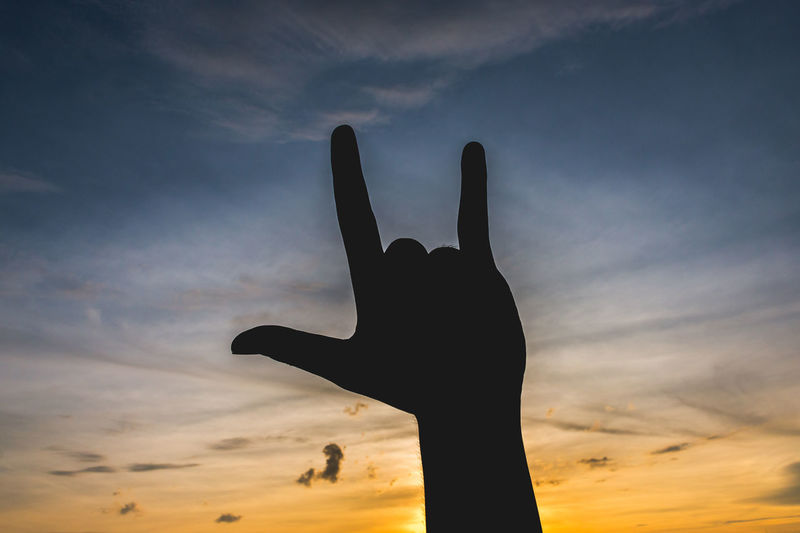 Cropped image of hand gesturing horn sign against sky during sunset