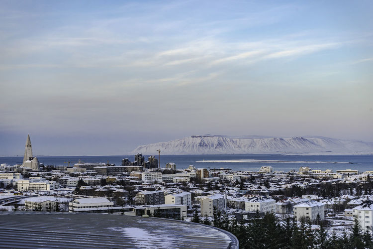 City view from Perlan City Center in Reykjavik, Iceland Blue Cityscape Harbor Iceland Mountain Reykjavik Sky Snow Snow Covered Mountain Tree View From Perlan City Center Deck In Reykjavik Iceland Water Wispy Clouds And Blue Skies Fresh On Market 2017