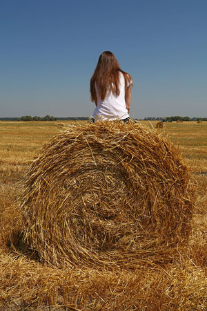 Young woman sitting on straw bale at remote wheat field Agriculture Bale  Casual Clothing Disconnected Discovering Field Hay Leisure Activity Lifestyles Nature On The Top Outdoors Remote Rural Rural Scene Sitting Sky Straw Thinking Tranquil Scene Tranquility Wheat Woman Young Woman People And Places Love Yourself