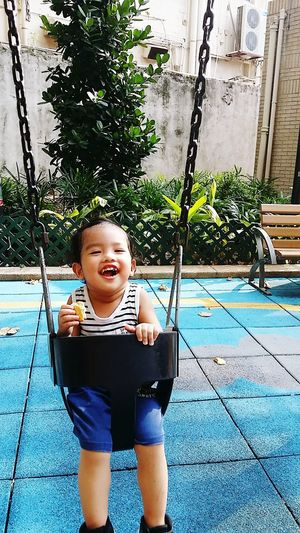 Happy Smiling Childhood Portrait Child Happiness Full Length Playing Cheerful Looking At Camera Outdoor Play Equipment Swing Babyhood Playground One Baby Boy Only Toddler  Preschooler Babies Only