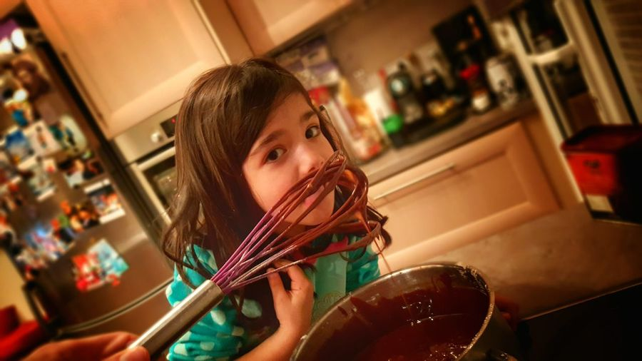 Portrait of girl licking chocolate in home
