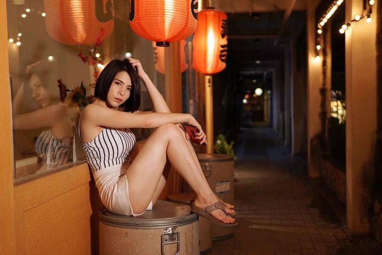 Full Length Portrait Of Woman Sitting In Alley At Night