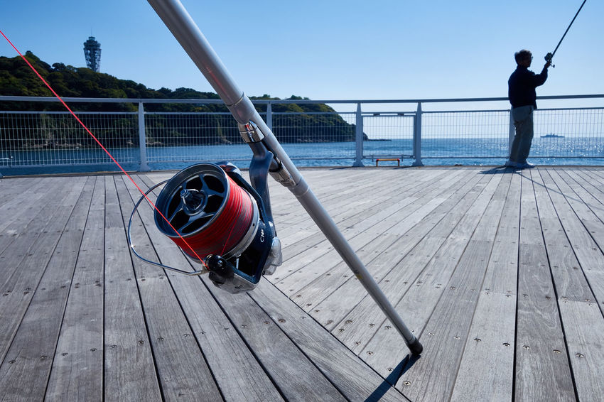 Clear Sky Close-up Day Sports Fishing Standing Focus Object Focus On Foreground Full Length Harbor Leisure Activity Men Nature One Person Outdoors People Pier Real People Sea Sea And Sky Seascape Sky Sport Water Wood - Material Weekend Activities