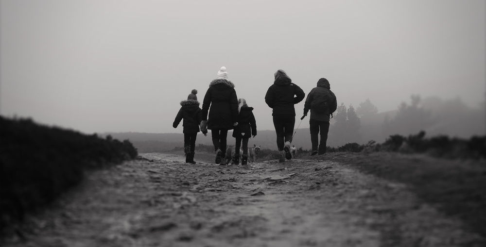 Rear View Of Family Walking On Footpath At Moel Famau Against Sky During Winter