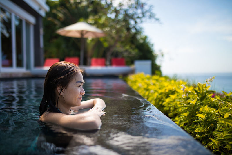Side view of woman relaxing in infinity pool