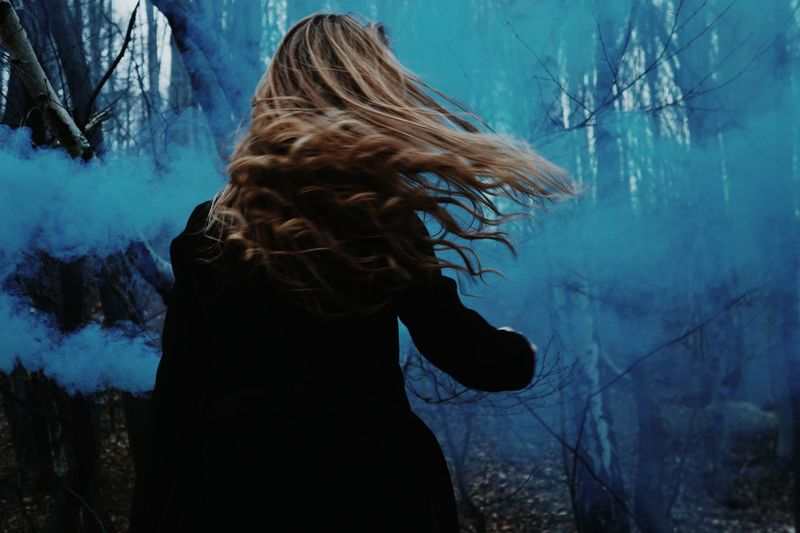Rear view of woman with tousled hair against blue distress flare in forest