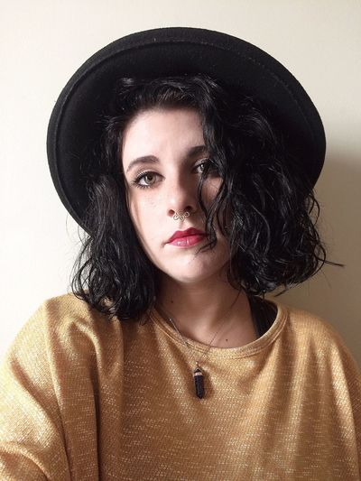 Portrait of young woman in hat sitting against wall at home