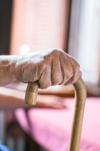 Elderly person's hand holding a walking stick