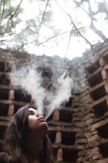 Low Angle View Of Thoughtful Woman Smoking Against Wall