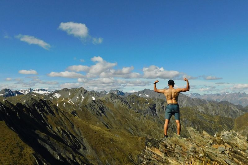 Shirtless man flexing muscles while standing on mountain against sky
