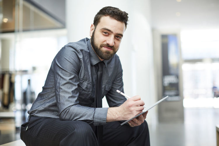 Young bearded Brazilian man works on an iPad in New York City Beard Brazilian Businessman Confidence  Corporate Business Digital Tablet Finance Inside Ipad Light Looking Man Mobile Modern One Man Only One Person Only Men Sitting Tablet Technology Tie Touch Screen Web Design Well-dressed Working
