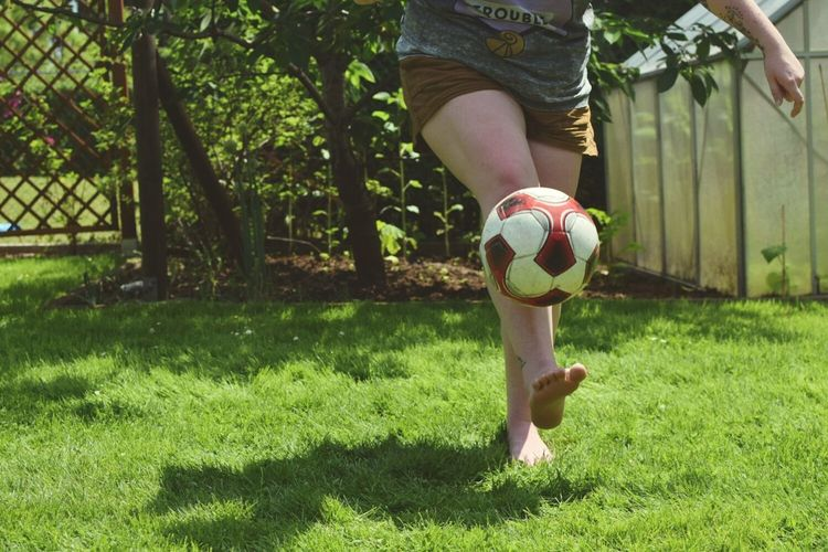 Low Section Of Woman Playing Football On Field