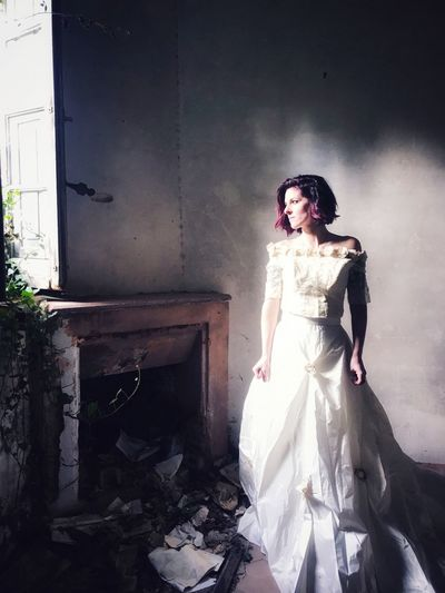 Portrait of young woman standing against abandoned building
