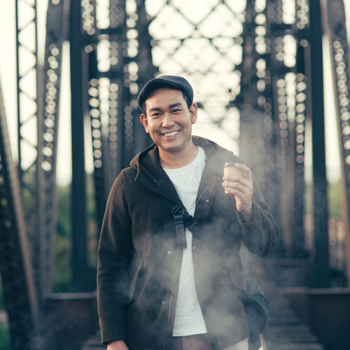 Portrait of smiling man standing on bridge
