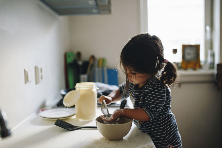 Side view of girl preparing food on kitchen counter at home