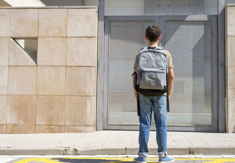 Rear view of boy with backpack standing against metal door during sunny day