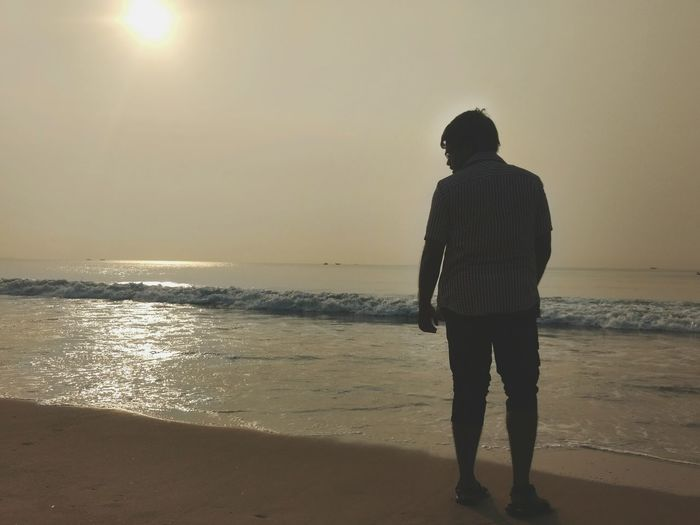 Rear view of silhouette man standing on beach