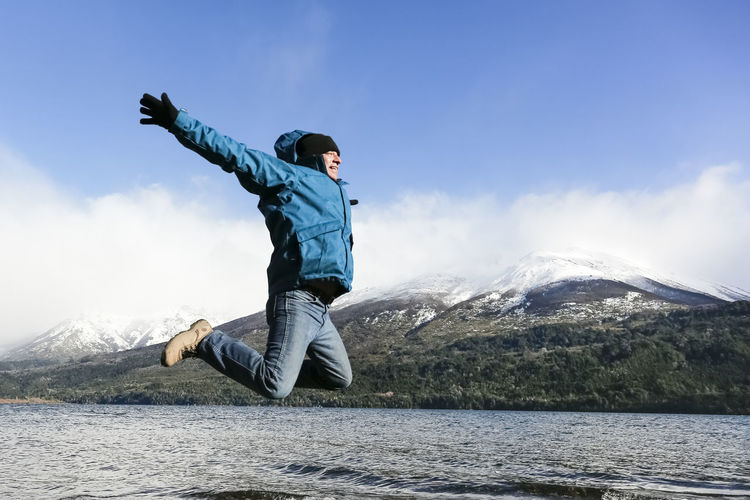 Male Tourist Jumping With Outstretched Arms