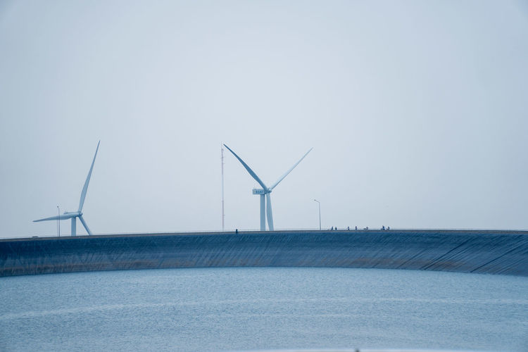 Wind turbines on landscape against clear sky