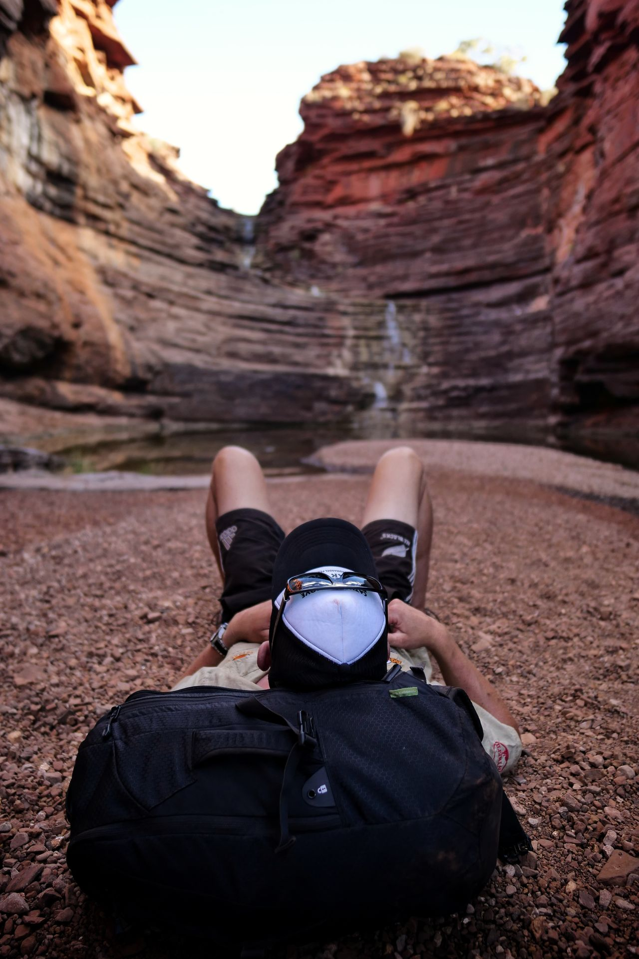 Rear view of man lying on desert against rock formations