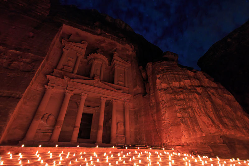 Illuminated candles glowing against temple at night