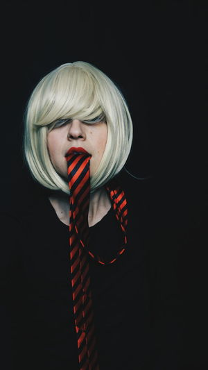 Portrait Of Mid Adult Woman With Tie In Mouth Against Black Background