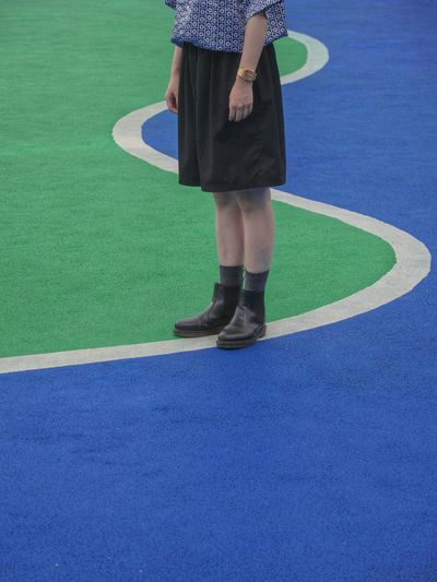Low section of woman standing on green ball