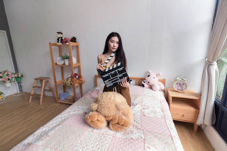 Full length of woman sitting on bed at home