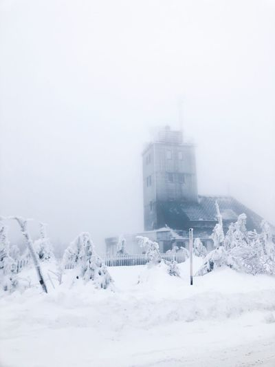 Buildings on snow covered land against sky