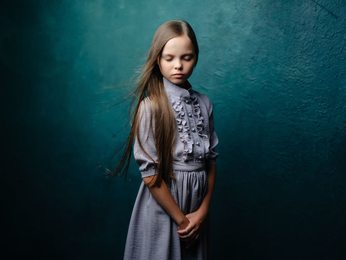 Portrait of teenage girl standing against blue wall