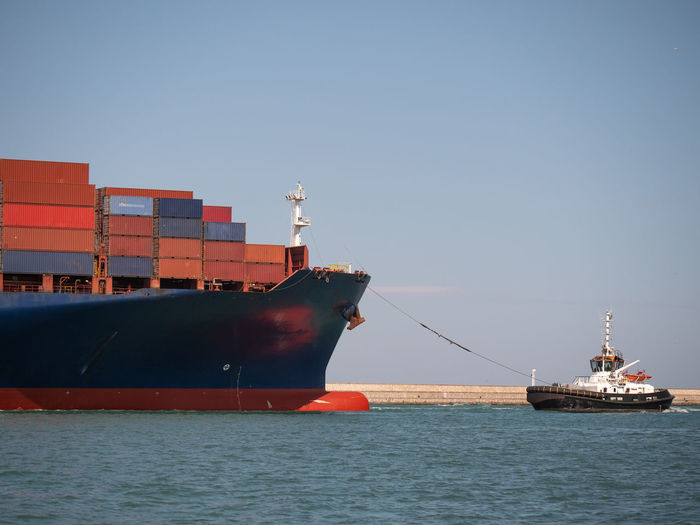Large container ship towed into port by a small tugboat.