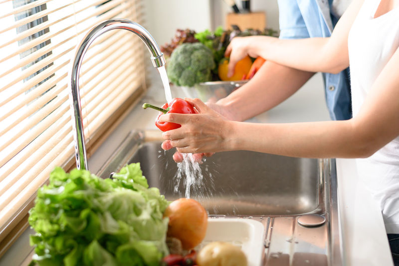 Midsection of woman preparing food in kitchen at home