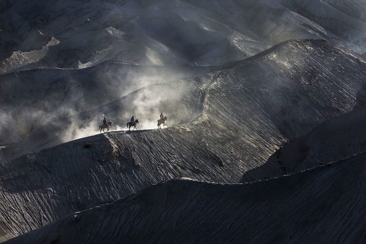 High angle view of people riding horses on mountain peak